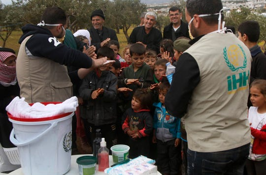 This file photo released by the Turkish humanitarian group IHH on April 6, 2020, aid workers of the group demonstrate to Syrian children how to properly wash hands, at a camp for internally displaced persons in northern Syria.