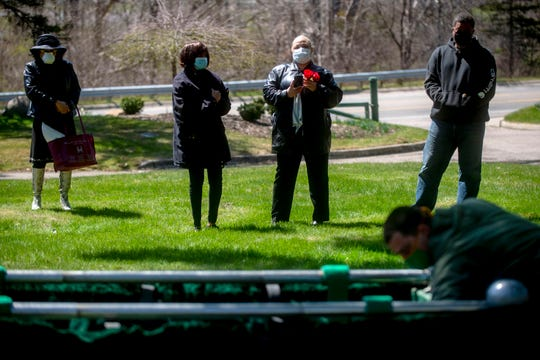 Family members watch as the casket of World War II veteran Ferrald Fredie Waller is lowered into the ground during a funeral service on Monday, April 20, 2020 at River Rest Cemetery in Flint Township, Mich.