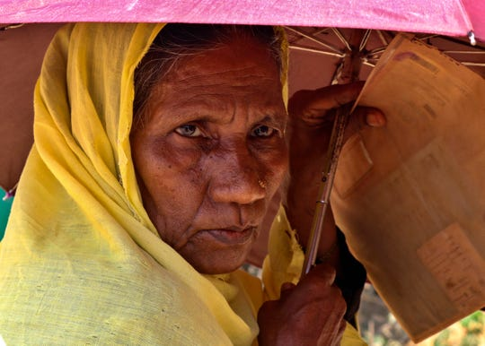 In this April 15, 2020 photograph, a Rohingya refugee woman holds an umbrella as she waits to collect food aid at the Kutupalong refugee camp in Cox's Bazar, Bangladesh.