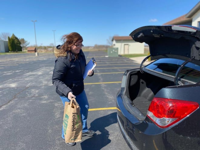A We Care Food Pantry at the Grace Christian Church volunteer takes a bag of food out to a vehicle.