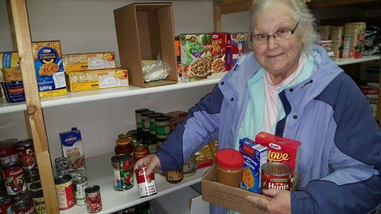 Lighthouse Christian Church Food Pantry volunteer Diann Krusz putting a food box together.