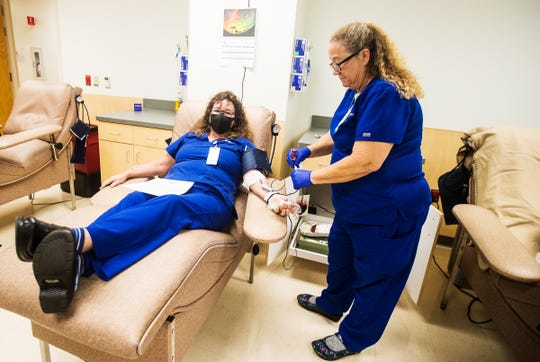 """Jennifer Zavodny, left, donates convalescent plasma with the help of Bonnie Hill, a blood nurse at Lee Memorial Hospital. Zavodny recovered from a milder case of COVID-19 and is the first Lee County resident to donate plasma for Mayo Clinic's study of """"convalescent plasma"""" for a potential therapy for COVID-19 patients."""