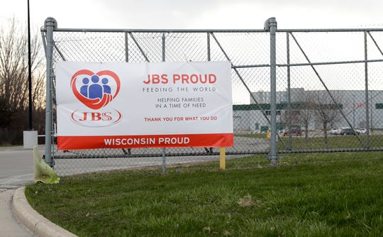 "A sign saying ""JBS Proud"" hangs on a fence at JBS Packerland on Lime Kiln Road April 17, 2020, in Green Bay, Wis."