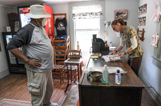 Johnny Jones of Greenwood buys ribs from Jessica Bell in the store at Split Creek Farm in Anderson Wednesday.