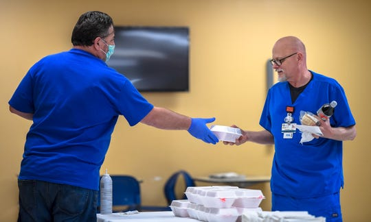 "Doros Hadjisavva hands Registered Nurse Randall Hurt a free gyro Wednesday. Doros and his wife Ellada were providing ""Gyros for Heroes"" and plan to continue their giving at health-care sites in Evansville in the weeks to come."