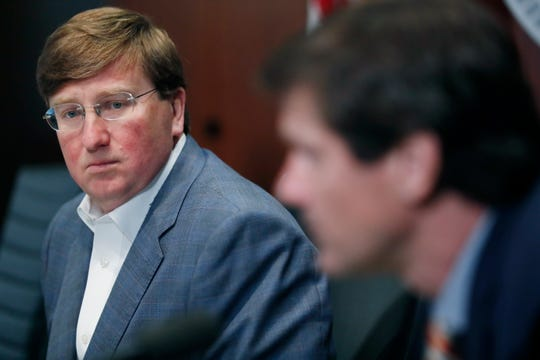 Gov. Tate Reeves, left, looks toward State Health Officer Dr. Thomas Dobbs at a recent news conference.