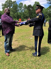 Marcus Johnson, the son of Robert Thompson Jr., is presented with a service flag at his father's funeral. Thompson Jr. was killed in a tornado that struck Bassfield, Miss., on Easter Sunday, April 12, 2020.