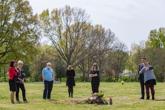 Family members of Barbara Wilding, who died of COVID-19 early Monday morning at the age of 81, look on following her burial at the Louisville Memorial Cemetery on Wednesday.