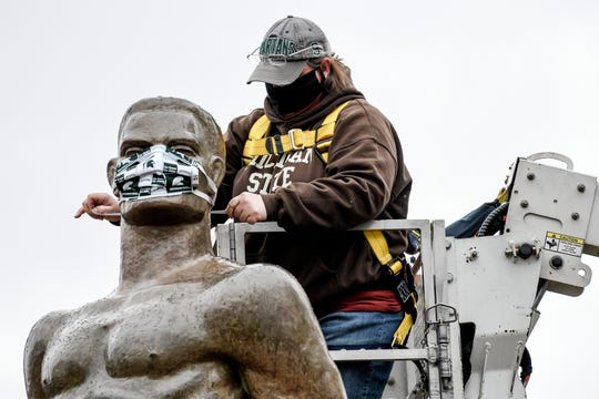 Michigan State University Infrastructure Planning and Facilities Landscape Services utility worker Kimberly Consavage ties a mask on the Sparty statue on Wednesday, April 22, 2020, on the Michigan State University campus in East Lansing. The mask was put on as a way to spread awareness in slowing the spread of the coronavirus.