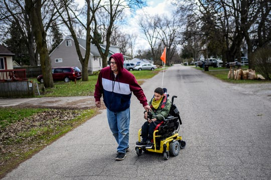 Brian Hagler, left, and his son, Chris, 8, walk down the street outside their home while out for some fresh air during Brian's break from work on Tuesday, April 21, 2020, in Lansing. Chris used speech, physical and occupational therapies provided by his school before the coronavirus outbreak restrictions.
