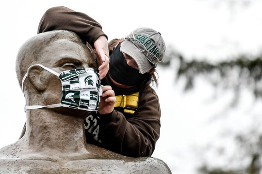 Michigan State University Infrastructure Planning and Facilities Landscape Services utility worker Kimberly Consavage adjusts a mask on the Sparty statue on Wednesday, April 22, 2020, on the Michigan State University campus in East Lansing. The mask was put on as a way to spread awareness in slowing the spread of the coronavirus.