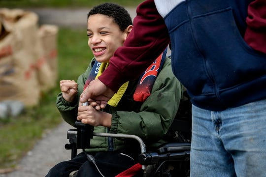 Brian Hagler, right, helps his son, Chris, 8, with steering his wheelchair while out for some fresh air during Brian's break from work on Tuesday, April 21, 2020, in Lansing. Chris used speech, physical and occupational therapies provided by his school before the coronavirus outbreak restrictions.