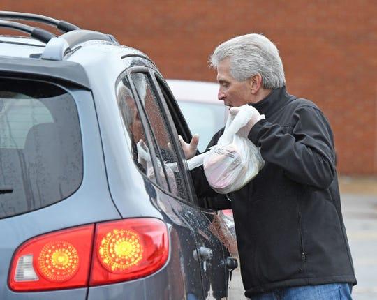 Lexington superintendent Mike Zieglhofer passes out free lunches Monday, March 23 at Lexington High School.