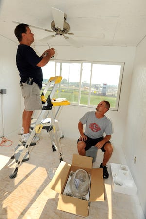 Elgin High School Athletic Director Jason Hix, right, and his father, Dick Hix, install fan and light fixtures for the new press box at Elgin's football stadium in 2012. This year Jason Hix's son Justin is a senior and was a member of the baseball team.