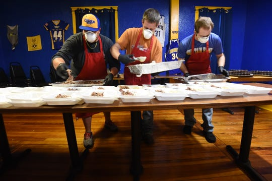 Holy Smokes BBQ owner Matt Wood, left, and employees Ray Spangler, center, and Jon Sipe prepare some of the 200 meals the restaurant delivered to Baxter Regional Medical Center employees on Wednesday as part of the ongoing MH Cares initiative to feed the community and support restaurants.