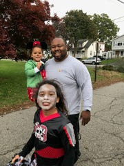 """Darell was known as a """"good family man."""" He holds Maycie, 4, as they walk with Emma, 9."""