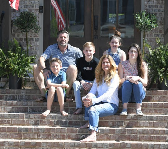 Brian and Jennifer Carroll with their four children, Sydney, 14, Tucker, 13, Olivia, 11, and John, 10, on their Franklin front porch.
