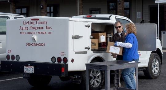 Dave and Joy Martin load food and care packages into Joy's truck before she heads out to deliver meals to seniors throughout the county for the Licking County Aging Program on Wednesday, April 22, 2020.
