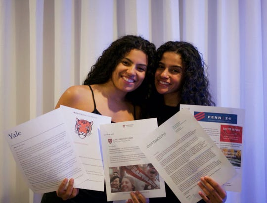 Clifton High School seniors Jessica (L) and Nicole Alexander holding acceptance letters from five Ivy League Schools.