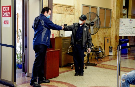 Paterson Mayor Andre Sayegh first bumps with security guard Victor Tinea as he enters City Hall for the first time since recovering from Covid-19, Sayegh quarantined in his Paterson home for two weeks and tested negative for the coronavirus prior to returning to work on April 22, 2020.