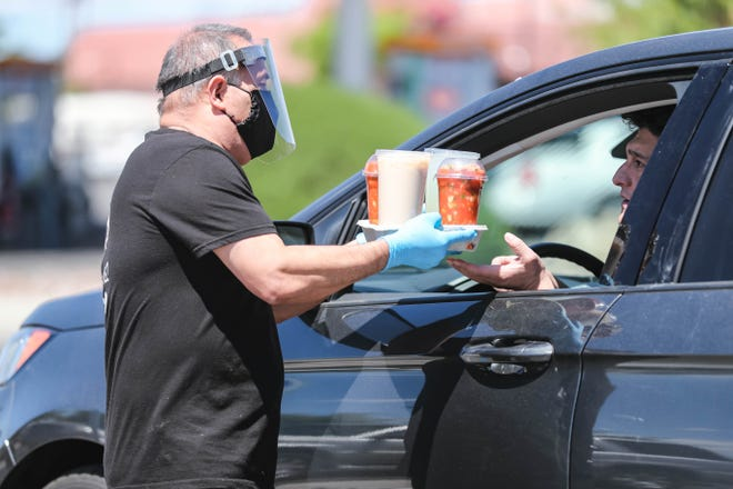 Gonzalo Chavez takes out orders to customers while wearing a mask and face shield at Taqueria Chavez in Las Cruces on Wednesday, April 22, 2020.