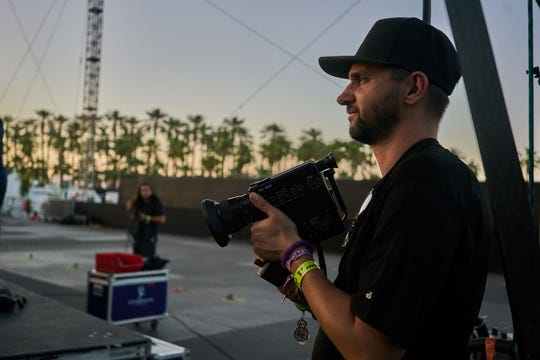 """Chris Perkel, director and producer of """"Coachella: 20 Years in the Desert"""" holds a camera while working."""