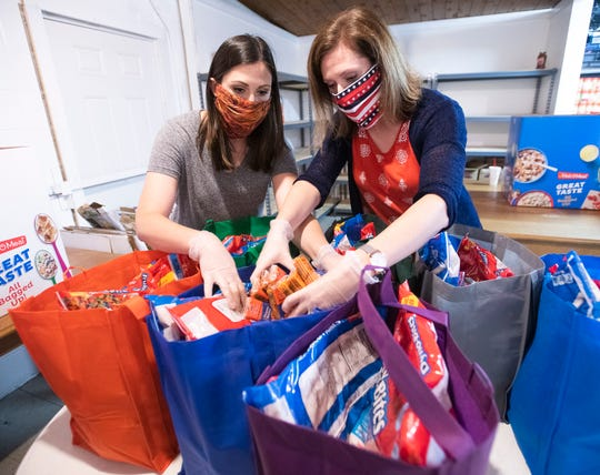 Brooke Scott and April Davis prepare food kits for distribution to under-served students in Santa Rosa County on Wednesday. The nonprofit group FoodRaising Friends is holding a drive-thru food drive and is asking for donations to be dropped off from 9 a.m. to 5 p.m. Friday at The Cutting Board, 5701 U.S. 90 in Milton.