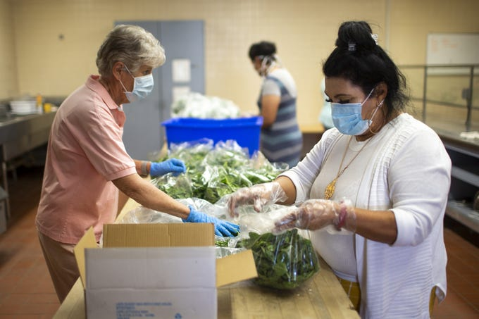 Joan Brunner (left) and Sandra Amarillas (right), both members of the nonprofit Unlimited Potential, bag spinach at the Brooks Community Center in Phoenix on April 22, 2020. The nonprofit was bagging produce to be delivered to families and senior living homes in Phoenix.