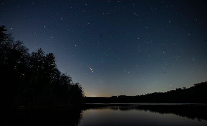 A lone meteor from the Lyrids shower briefly streaks across the sky above Lake Williams early Wednesday morning, the 50th anniversary of Earth Day.Wednesday, April 22, 2020.John A. Pavoncello photo