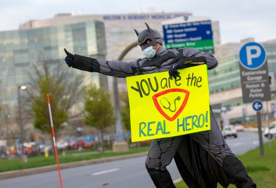 Chuck Brooks, a registered nurse in the Medical Intermediate Care Unit, dressed up as Batman and greets employees as they come in to work at Penn State Health Milton S. Hershey Medical Center and Penn State College of Medicine on Tuesday, April 14, 2020.