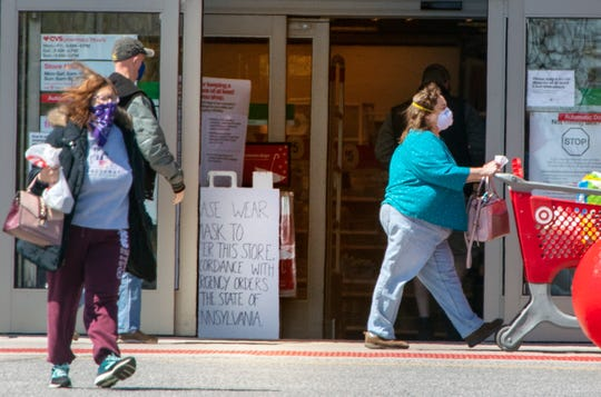 Masked shoppers exit and enter Target in West Manchester Township while a sign warns them at the entrance that masks are mandatory in accordance with Pennsylvania state orders.