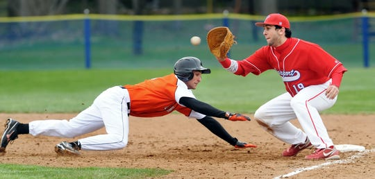 Churchville-Chili's Andrew Michaels, left, dives safely back to first before the pickoff attempt reaches Fairport's Conner Simonetti during regular season game played at Fairport High School on Friday, March 30, 2012.  Fairport won the game 9-2.