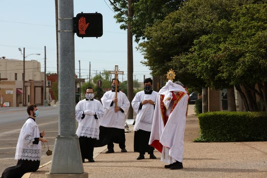 Seminarians of the Roman Catholic Diocese of San Angelo are joined by Vocation Director Fr. Michael Rodriguez in offering a blessing on Shannon Medical Center in downtown on Sunday, April 19, 2020.