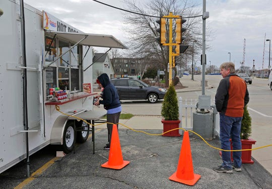 Patrons at Sparky's Hot Dog Stands observe social distancing while waiting to order their food, Wednesday, April 22, 2020, in Sheboygan, Wis.