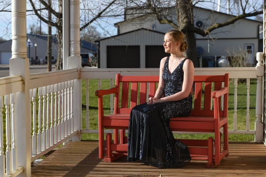 "Canistota High School junior Saylor Hutcheson wears her prom dress on her front porch on Saturday, April 18, in Sioux Falls. On what would have been prom night, Saylor decided to dress up anyway, even though she would just be eating dinner and watching a movie with her family. ""All my siblings were watching me get ready,"" Saylor said. ""I at least wanted to wear my dress on prom night."""