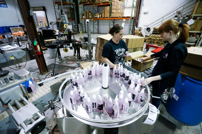 Aire-Master employees Nita Moore (left) and Ashley Roush package bottles of hand sanitizer on a production line on Wednesday, April 22, 2020.