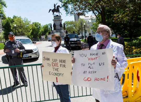 Erich Bruhn, MD, right, and Kristin Bruhn, center, of Winchester, Va., hold up signs against reopen Virginia protest at the Virginia Capitol Square in Richmond, Va., on Wednesday, April 22, 2020. (Daniel Sangjib Min/Richmond Times-Dispatch via AP)