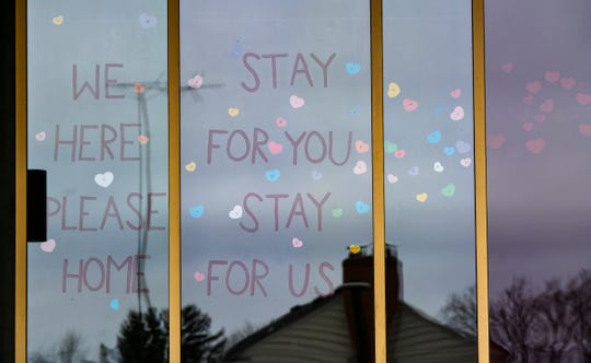 """Hearts surround a message on the windows of St. Cloud Hospital as part of the """"A World of Hearts"""" movement Friday, April 3, 2020, in St. Cloud."""