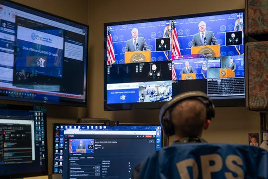 Josh Knodle of the Department of Public Safety managed the live feed of Governor Walz press conference as Gov. Tim Walz and leaders from Mayo Clinic, the University of Minnesota, and other Minnesota health system leaders announced advances for COVID-19 testing in Minnesota. (Glen Stubbe/Star Tribune via AP, Pool)