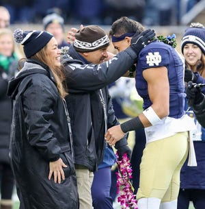 Alohi Gilman (right) and his father Asai (middle) on Notre Dame's Senior Day against Boston College on November 23, 2019.