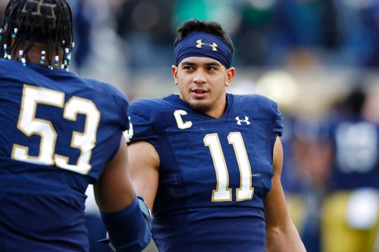 Notre Dame safety Alohi Gilman (11) greets defensive lineman Khalid Kareem (53) before the first half of an NCAA college football game, Saturday, Nov. 2, 2019, in South Bend, Ind. (AP Photo/Carlos Osorio)