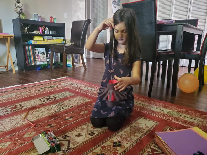 Arvaneh Shokirov, age 7  makes paper lanterns during Ramadan at her home. Traditional gatherings are interrupted this year during the month of Muslim fasting.