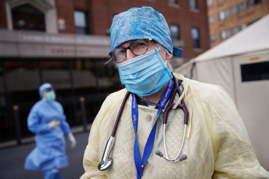Catherine Hopkins, Director of Community Outreach and School Health at St. Joseph's Hospital, stands outside a COVID-19 triage and testing tent, Monday, April 20, 2020, in Yonkers, N.Y. (AP Photo/John Minchillo)