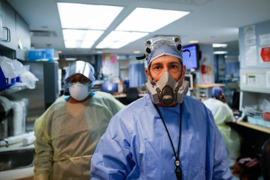 Dr. Anthony Leno, director of emergency medicine, pauses after he and his staff save the life of a COVID-19 patient who suddenly went into cardiac arrest, Monday, April 20, 2020, at St. Joseph's Hospital in Yonkers, N.Y. The patient survived the ordeal. (AP Photo/John Minchillo)