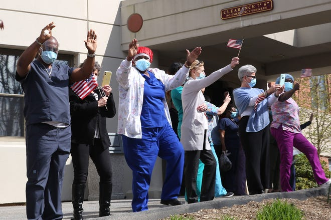 Some argue that the best-run nursing homes in New York state performed best against the coronavirus. But the state health department refutes that, saying they found no correlation between quality of care and coronavirus cases. Here, health care workers wave at passing parade that saluted medical workers back in April.