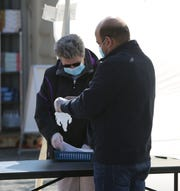 Dheeraj Katanguri (right) prepares to pass testing materials to a patient at a drive-thru coronavirus testing site in Smyrna.