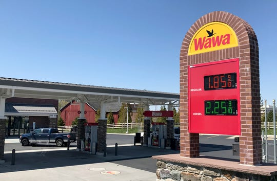 People use the gas pumps at a Wawa location on Concord Pike Wednesday.