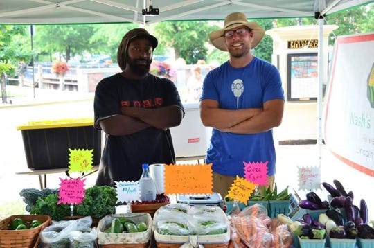 Curtis Hamm, left, and Joshua Nash at their farmers market stand.
