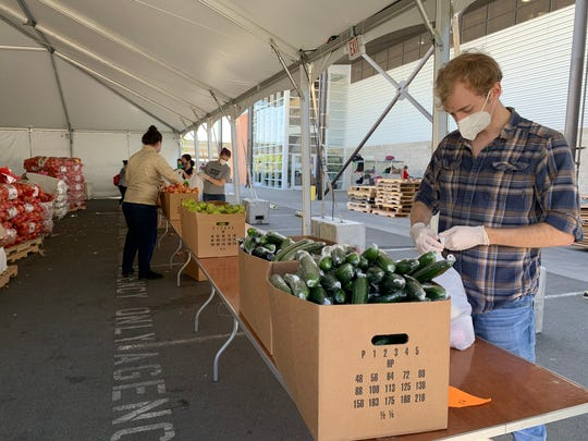 Volunteers at the San Francisco-Marin Food Bank fill bags of fruit and produce for people who are food insecure. The food bank has seen need increase during the COVID-19 emergency.