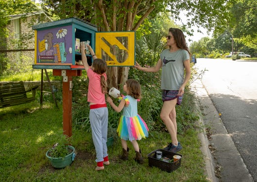 Sheila Parr and her daughters Violet Cann, left, 7, and Stella Cann, 5, donate food and toilet paper to the Little Free Library on Princeton Drive in Austin, Texas, on Tuesday April 21, 2020.  In response to the coronavirus pandemic, many of the book exchange boxes around the U.S. are being repurposed as sharing boxes with free food and toilet paper.